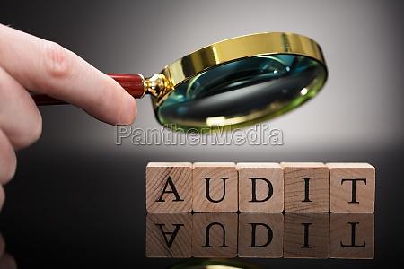 person examining audit blocks through magnifying