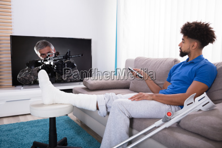man with broken leg watching television