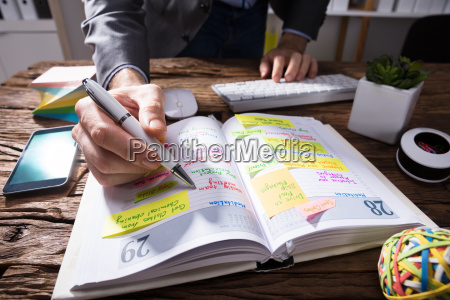 businesspersons hand writing schedule in diary