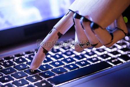 robot typing on laptop