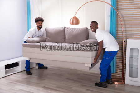 two male movers placing the sofa