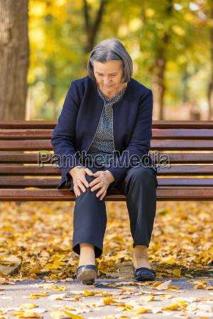 senior woman having knee pain walking