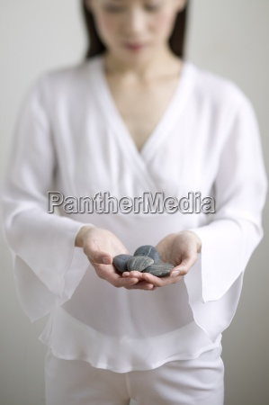 young woman holding stones