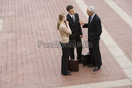 three business people talking outdoors