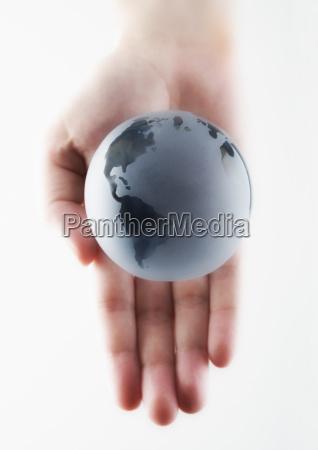 hand holding a miniature globe