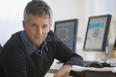 businessman leaning on desk