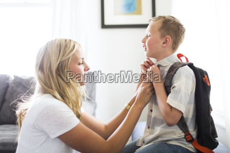 mother helping son 6 7 buttoning