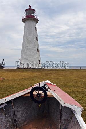 old rowboat against lighthouse