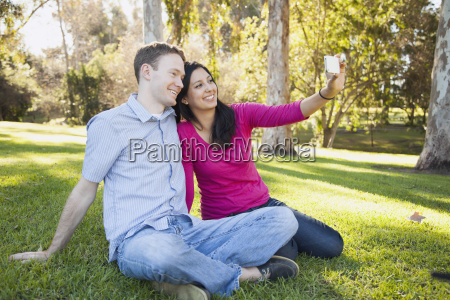 couple sitting on grass in park