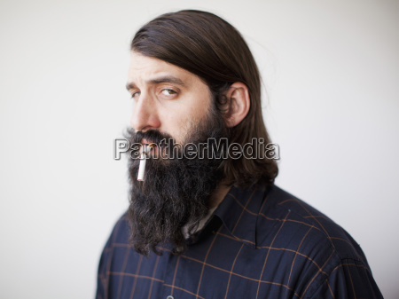 bearded young man with broken cigarette