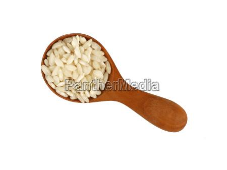 white arborio rice in wooden scoop
