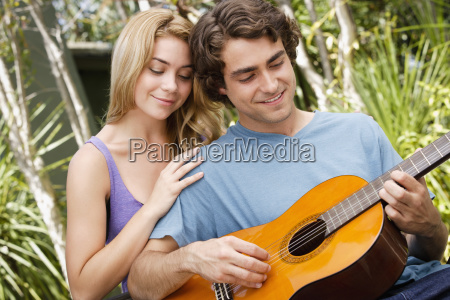 young couple in park man playing