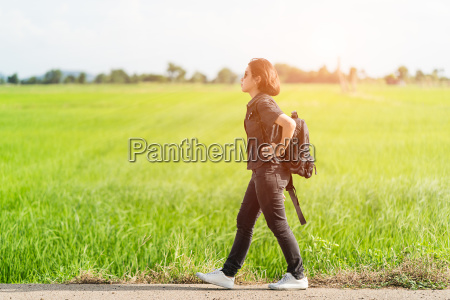 woman with backpack hitchhiking along a