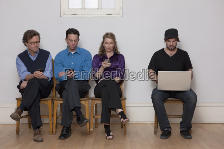 four people sitting in a row