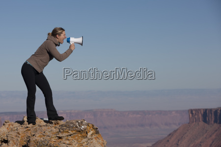 woman yelling into megaphone at top