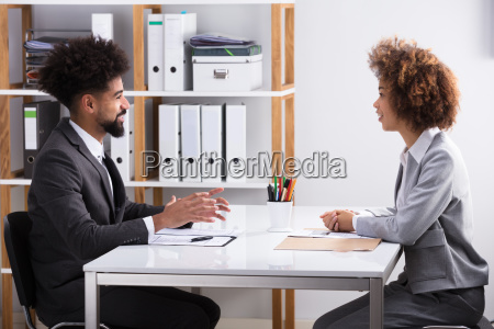 two businesspeople having conversation in office