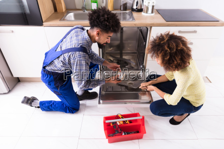 repairman fixing dishwasher in kitchen