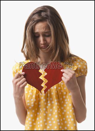 teenage girl holding broken heart