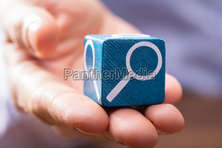 persons hand holding blue wooden block
