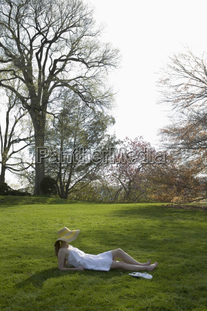 a woman lying on grass outdoors