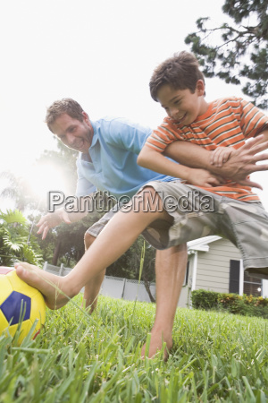 father and son playing soccer in