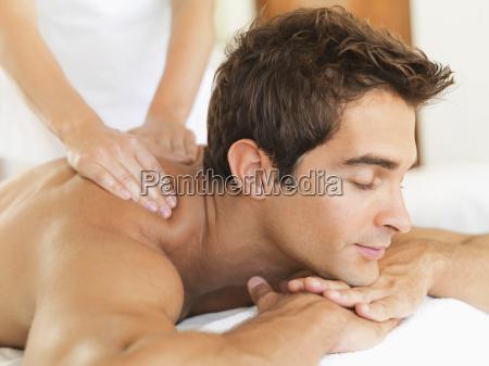 man receiving massage in spa