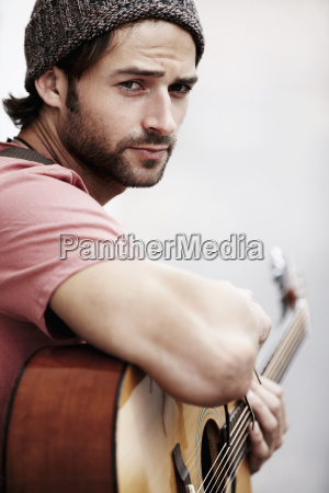 portrait of musician playing guitar outdoors