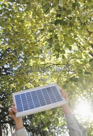 hand holding solar panel in park