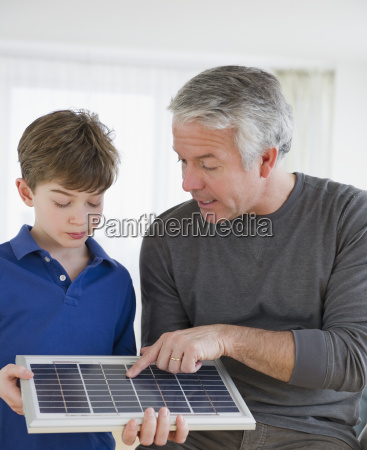 father showing solar panel to son