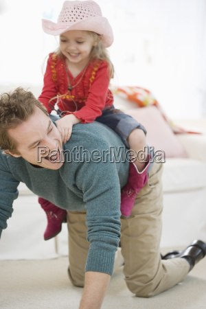 father and daughter playing in livingroom