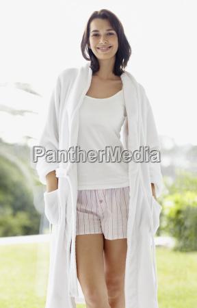 smiling brunette woman wearing a bathrobe
