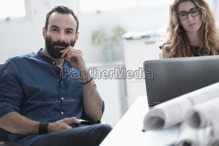 man and woman talking in office