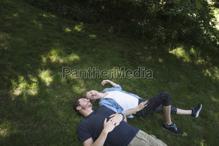 couple lying on grass in forest
