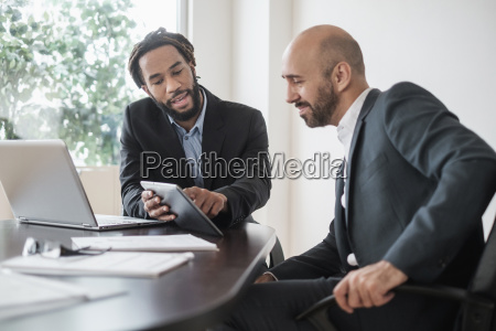 two businessmen working with digital tablet
