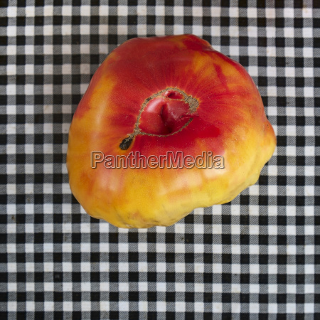 heirloom tomato on checkered tablecloth