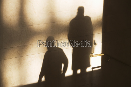 shadow of two male pedestrians on