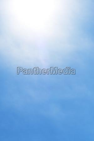 sun behind small cloud on blue