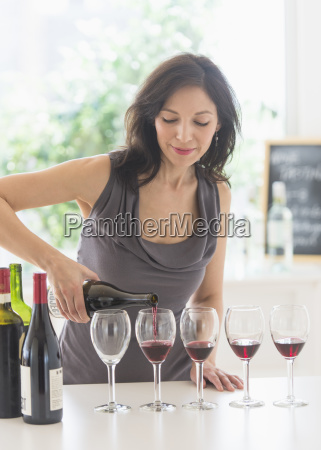 woman purring red wine into wine