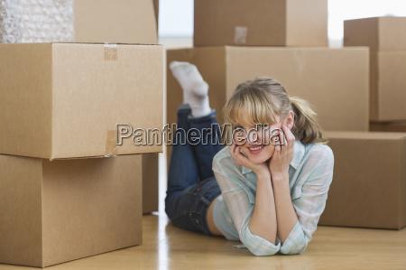 woman lying among cardboard boxes during