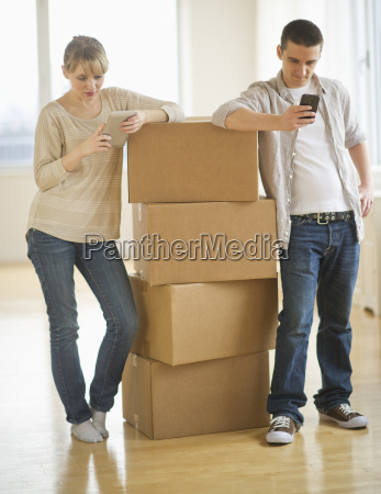 couple leaning on cardboard boxes during
