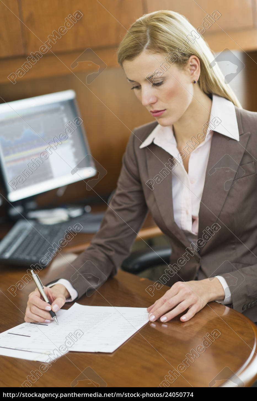 businesswoman, writing, at, desk - 24050774