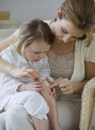 mother putting bandage on daughters knee