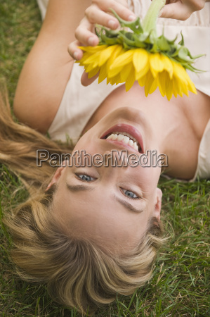 woman laying in grass holding sunflower