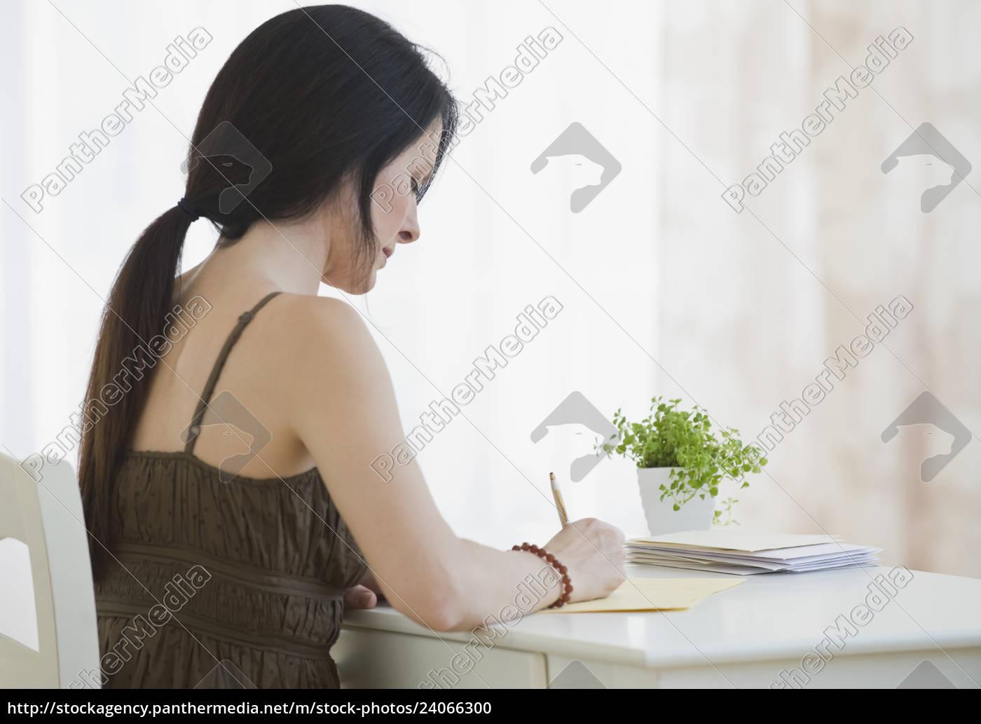 woman, writing, at, desk - 24066300