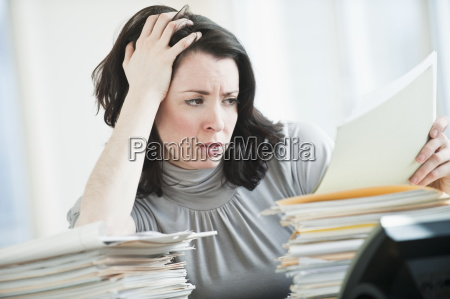 stressed business woman reading paperwork in