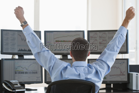 male trader raising arms in success