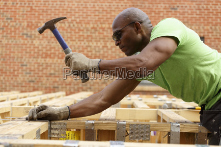 black man hammering nail at construction