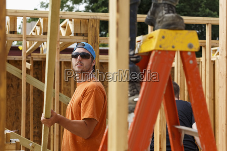 caucasian man lifting lumber at construction