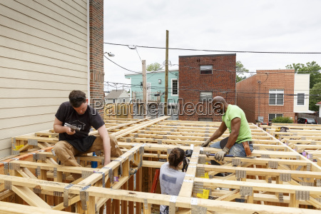 volunteers hammering nails at construction site