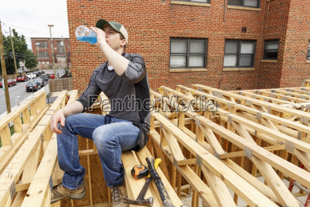 caucasian man drinking beverage at construction